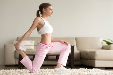 Beautiful young woman in sportswear standing on one knee and doing quad stretches in living room, warming up muscles before fitness workout at home, strengthen tendons and ligaments, good flexibility