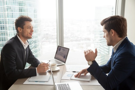 Two businessmen discussing company financial strategy or marketing research during meeting at desk in office. Business partners deciding how to improve profitability and accelerate investments return