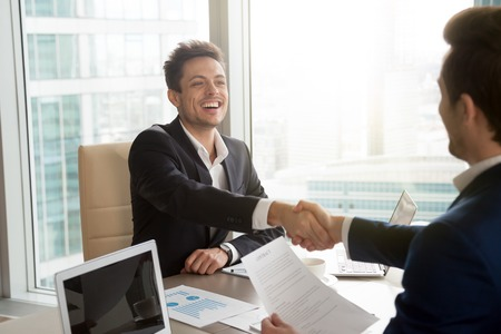 Satisfied successful businessman shaking hand with his business partner after conclusion of profitable contract. Happy smiling entrepreneur congratulating colleague with good deal, starting partnership