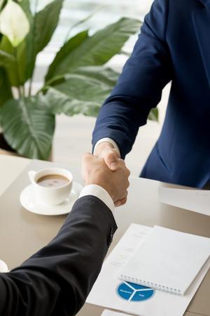 コーヒーカップとビジネス文書とデスク上のビジネスマンの握手の画像を閉じます。交渉中に信頼を示すビジネスパートナー、会議を歓迎し、握手