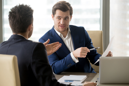 clarifying: Successful businessman clarifying provisions of contract with business partner, discussing terms of agreement, explaining strategy or financial plan. HR manager asking job candidate about his resume
