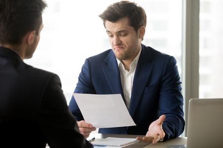 Ontevreden over contractvoorwaarden is de zakenman het niet eens om voorwaarden van twijfelachtige overeenkomstvergadering met zijn zakenpartner op kantoor te accepteren. Teleurgestelde investeerder niet onder de indruk van het aanbodconcept