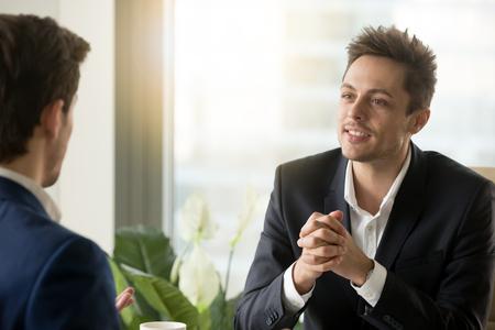 Portrait de bel homme d'affaires ayant offre intéressante de partenaire d'affaires assis en face. Un employé du millénaire en costume d'affaires discute avec un collègue et écoute l'opinion personnelle de ses collègues Banque d'images - 85500462