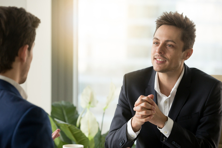 Portrait of handsome businessman getting interesting offer from business partner sitting opposite. Millennial employee in business suit talking with colleague, listening coworkers personal opinion Stock Photo