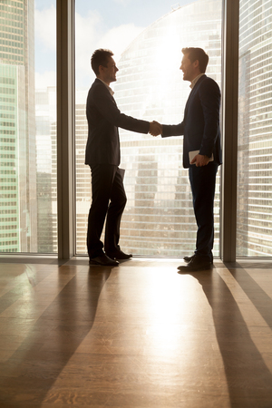 Successful businessmen shaking hands when standing near large window with urban cityscape outside. Business partners welcoming each other while meeting in office, congratulating with career promotion