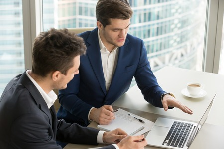 Confident financial consultant or adviser presenting promising project to client with laptop, explaining details of investment partnership, revealing conditions of partners offer. Businessmen meeting Stock Photo