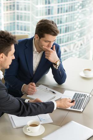 オフィスで重要な企業プロジェクトに協力しながらラップトップを使用するビジネスパートナー。有望な取引の提示を行う顧問投資専門家に耳を傾