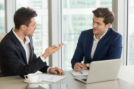 사무실에서 책상에 앉아있는 동안 비즈니스 파트너에게 자신의 제안을 설명하는 사업가, 협력 및 푸싱, 계약의 전망을 토론 노력의 이점에 대해 이야 스톡 콘텐츠