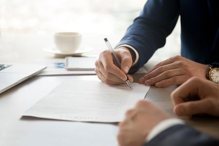 ビジネスパートナーの存在下で契約書に個人的な署名を置くビジネスマンの手のクローズアップ画像。起業家や会社との成功したパートナーシップ