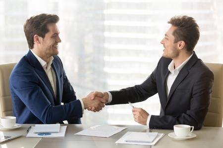 Gelukkige glimlachende partners die handen schudden en elkaar gelukwensen na het zingen van contract, succesvolle onderhandelingen, voordelige vennootschap, vertrouwen tussen bedrijfleiders, overeenkomst