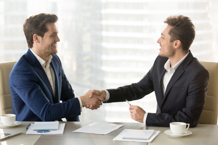 Happy smiling business partners shaking hands and congratulating each other after singing contract, successful negotiations, profitable partnership, trust between company leaders, conclusion agreement