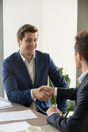 Successful businessman congratulating partner with great deal, offering partnership, introducing himself during important business negotiation. Director welcoming with handshaking new company employee Stock Photo
