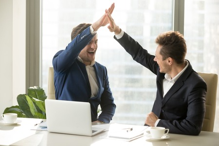Excited businessman smiling and giving high five to his business partner or colleague while sitting at meeting table in office. Happy entrepreneurs celebrating success, congratulating with achievement