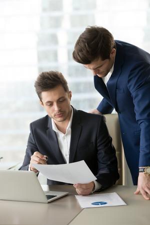 노트북을 사용 하여 책상에 앉아 하 고 비즈니스 문서를 표시하는 직원 기울고 관리자. 회사원, 프로젝트의 세부 사항을 설명하는 계획에 기능에 대해  스톡 콘텐츠