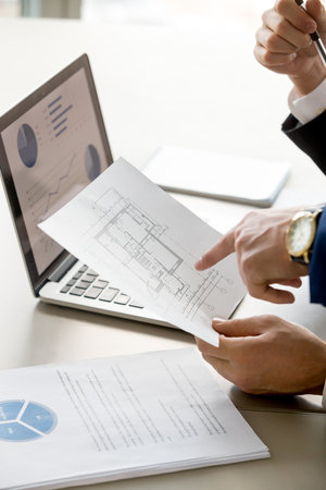 Sluit omhoog beeld van flats of huisplan in zakenmanhand, laptop met diagrammen op het scherm op achtergrond. Makelaar in onroerend goed bespreken waarde van onroerend goed. Architecten plannen bouwbudget