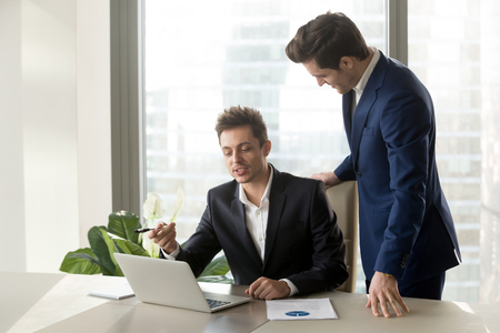 Employee sitting at workplace and explaining interesting idea to his boss. Executive manager standing near desk and listening proposal of economist about improving company efficiency and profitability
