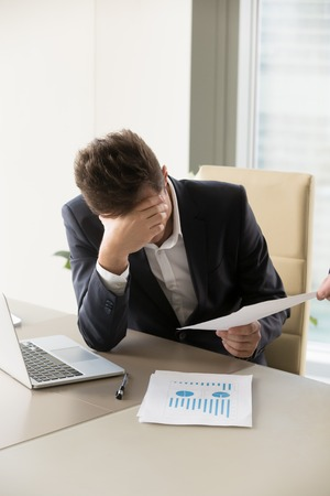 Frustrated businessman sitting at desk with laptop and business documents. Stressed entrepreneur upset because of low financial results, falling company shares value, bad statistics in annual report