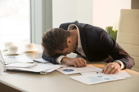 Tired businessman sleeping at workplace covered with documents. Overworked frustrated entrepreneur dozing, giving up after hard work day. Stressed CEO lying on desk shocked because of business failure