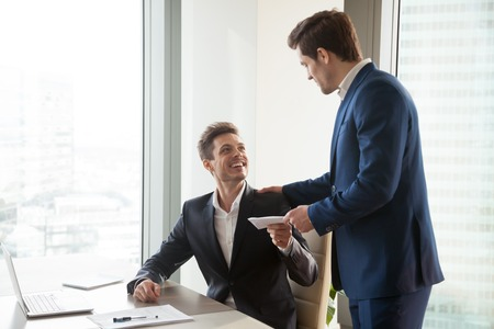 General manager presenting an envelope with premium or bonus cash to male company official. Boss congratulating happy employee with career promotion, thanking for good job and giving financial reward Archivio Fotografico