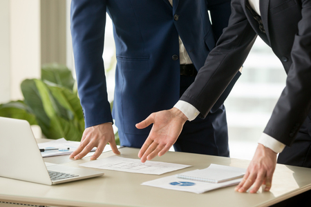 建設プロジェクトのプレゼンテーション中に机の上に横たわってアパートの図面を指してビジネスマン。建築家や不動産顧客と住宅計画を議論しま 写真素材