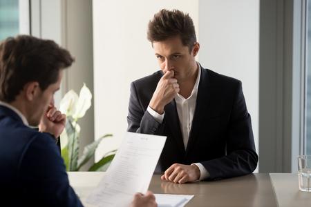 Zenuwachtige mannelijke baankandidaat die met worriment op personeelsalgemeentaar bekijkt die zijn samenvatting leest tijdens gesprek in bedrijfsbureau. Duizendjarige man die op zoek is naar een baan en solliciteert naar een vacature