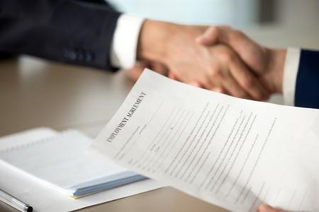 採用担当者の手で雇用契約書の写真をクローズアップジョブ候補の揺れ。申請者に仕事の契約を提供する雇用者、成功した面接、積極的な採用決定 写真素材 - 85500788