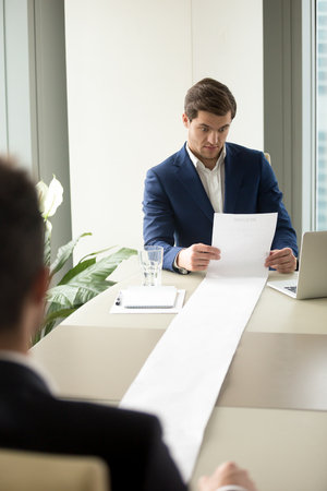 Executive recruiter looking surprised when reading applicants resume, shocked with long list of achievements, experiences and recommendations of job candidate, confused because of strange items in CV