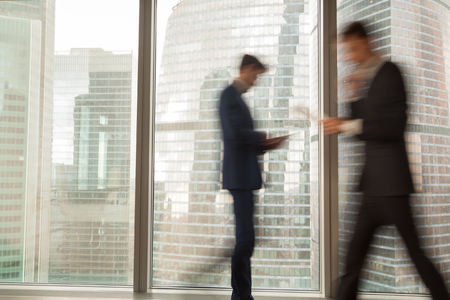 Image of blurry silhouettes of office workers hurrying in business past large window with city view in modern office. Fast and tense rhythm of modern business life, busy businessmen, economical grow Banco de Imagens