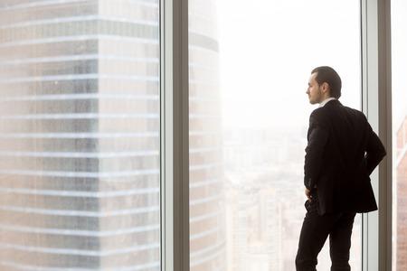 현대 도시 건물에서 창 밖을보고 위험한 금융 프로젝트를 고민하는 곧 비싼 양복 사무실에 서 서 걱정 된 또는 심각한 사업가, 곧 사업 거래에 [NULL]에