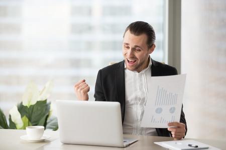 행복 한 잘 생긴 프로젝트 관리자 사무실에서 기념 하 고 행복 비명, 노트북 화면을보고 긍정적 인 재무 보고서를 들고. 주식 투자, 금융 승리 개념에