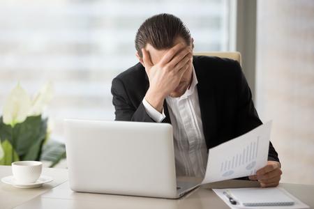 Beklemtoonde ongelukkige jonge zakenman in bureau voor laptop, houdend financieel document en facepalming in ongeloof wegens ontbrekende rapportstatistieken. Daling van de liquiditeit van aandelen, financiële verliezen