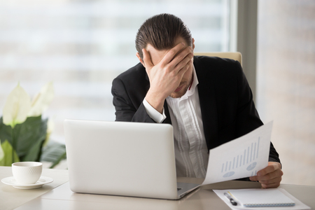 Stressed unhappy young businessman in office in front of laptop, holding financial document and facepalming in disbelief because of failing report statistics. Fall in liquidity of stocks, finance loss Stock Photo