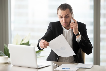 Shocked mad businessman in modern office talks on the phone holding financial report document, wrinkling his forehead in concern. Failing profit statistics, loss in stock market, bad decision concept. Stock Photo