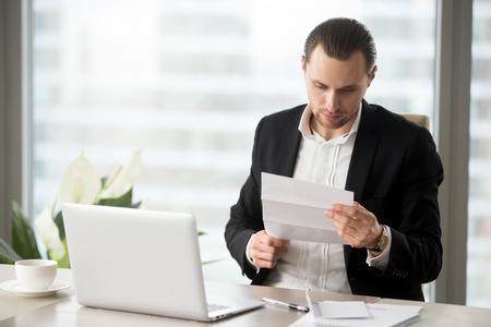 現代のオフィスで職場で重要な財務レターを読む若いハンサムビジネスマン。テーブルの上のラップトップ、ノート、コーヒーのカップ。事業提案