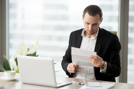 Young handsome businessman reading important financial letter at workplace in modern office. Laptop, notes, cup of coffee on the table. Business proposal concept, work correspondence, bill concept. Stock Photo