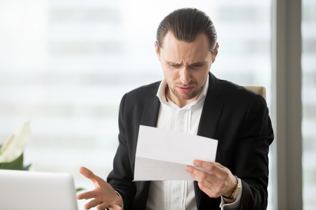 Frustrated young businessman in suit looking at confusing letter in modern office setting. Unexpected high bill, unpaid debt, failing financial report, tax delinquency, breach of contract concept. Stockfoto