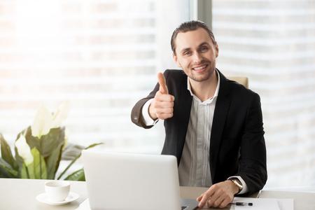 행복 한 미소 성공적인 잘 생긴 사업가 노트북 앞에 앉아 엄지 손가락을 보여주는 현대 사무실. 성공적인 거래 협상, 좋은 성과 결과, 투자 개념 만족.