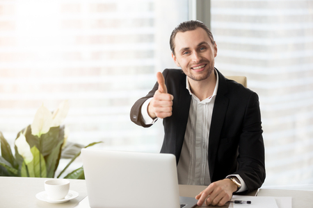 Happy smiling successful handsome businessman sitting in front of laptop, showing thumbs up in modern office. Successful deal negotiations, good work results, satisfaction with investment concept. Stock Photo