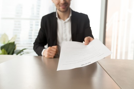 Smiling job applicant in suit handing over resume to recruiter during interview. Modern office setting. Recruitment manager giving resume back to candidate. Human resources, hiring, interview concept. Stockfoto