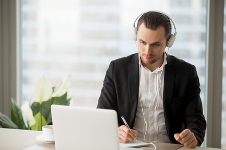 Thoughtful businessman in headphones taking notes in front of laptop at workplace. Young manager participating in online meeting or conference, remote job interview, learning foreign languages.