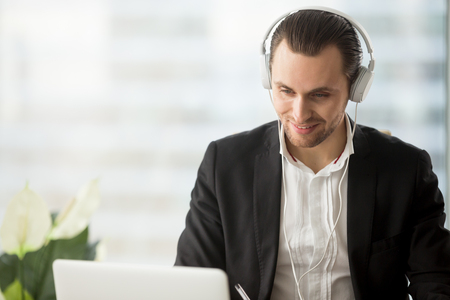 Smiling businessman in headphones looking at laptop screen at workplace. Friendly young manager participating in online meeting or conference, remote job interview, learning foreign languages.