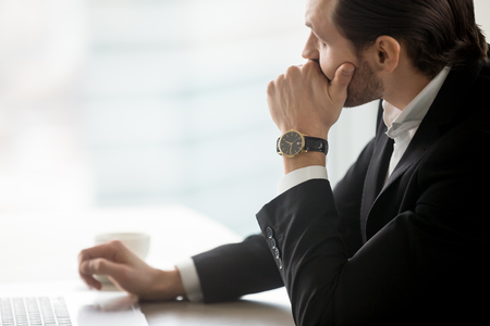 Serious concerned young businessman looks towards the window in deep thought sitting at workplace in modern office. Thinking about corporate future, work problem resolution, tough decision concept.