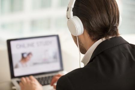 ヘッドフォンの男ノートパソコンで作業し、肩の上にバックビューをクローズアップ。ビジネスマン、プロジェクトマネージャー、オフィスワーカ