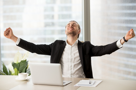 Smiling happy businessman raising arms up celebrating finished work project at workplace. Financial success, business interview successfully done, closing important deal, great stock news concept.