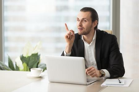 집게 손가락으로 노트북 앞에 앉아 프로젝트 관리자를 발생합니다. 젊은 기업가가 갑자기 책상에서 좋은 생각을했습니다. 성공적인 사업가 좋은 솔루