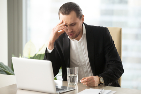 심한 두통, 진통제 치료 환 약을 보유하는 데 스트레스 사업가. 아픈 CEO와 머리 감기, 물 한 잔으로 약을 복용에 대 한 생각. 직장에서 아프다는 이유로  스톡 콘텐츠