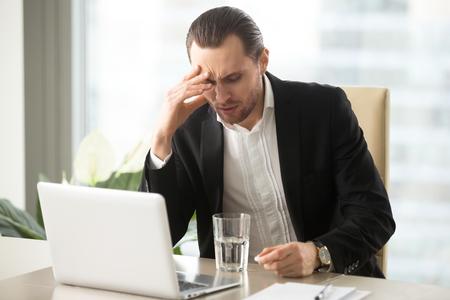 Uomo d'affari sollecitato che ha forte mal di testa, tenendo pillola rimedio antidolorifico. CEO malato con la testa fredda, pensando di prendere la medicina con un bicchiere d'acqua. Essendo malato sul lavoro, l'emicrania indotta dallo stress. Archivio Fotografico - 85638352