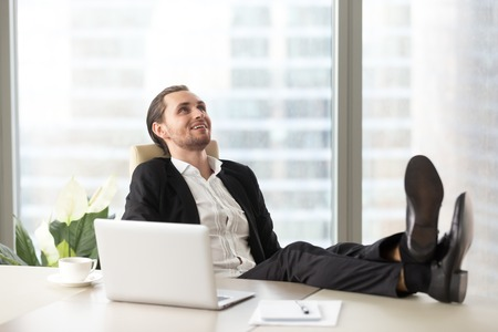 Happy smiling businessman relaxing, with legs up on desk at workplace in modern office. Dreaming about opportunities, taking break from workflow, chilling after good meeting, finished project concept.