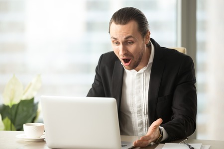 Frustrated young businessman looks at laptop screen screaming in anger at workplace in office. Unexpected high bill, unpaid debt, failing financial report, tax delinquency, breach of contract concept. Banco de Imagens - 85533836