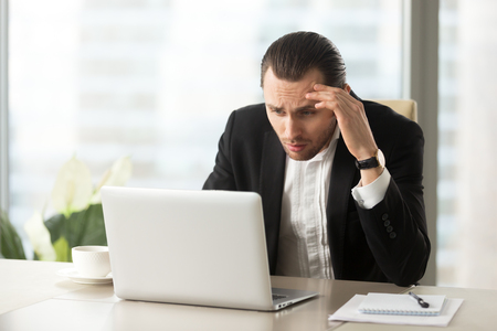 Upset confused businessman looking at laptop screen at workplace in modern office. Stressed young CEO at work desk looking at computer in disbelief about failing report statistics, bad mistake made. Banco de Imagens